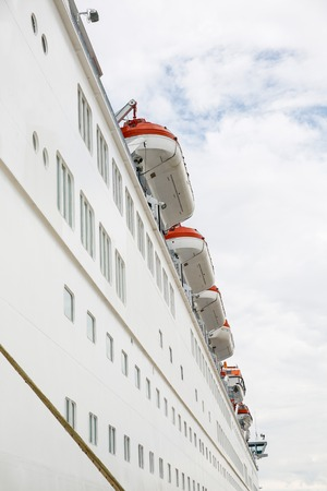 Big cruise ships hull with lifeboats in sight, docked in port for necessary maintenance, refill of supplies and sightseeing tour for passengers. Travel, hospitality and cruising business concept. photo