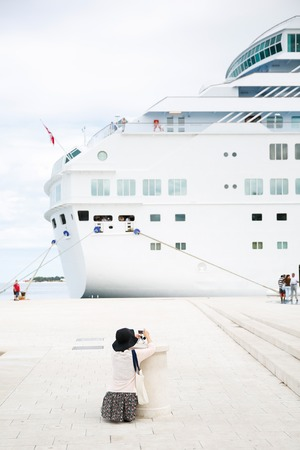 Tourist and passenger photographing a big cruise ship, docked in port for necessary maintenance, refill of supplies and sightseeing tour. Travel, hospitality and cruising business concept.