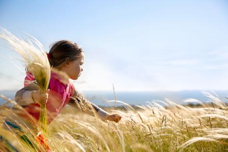 Schattig klein meisje het plukken en verzamelen bruine grassen op een weide met de wind waait door haar lange haren en de zee op de achtergrond. Allergie, hooikoorts en overgevoeligheid concept.