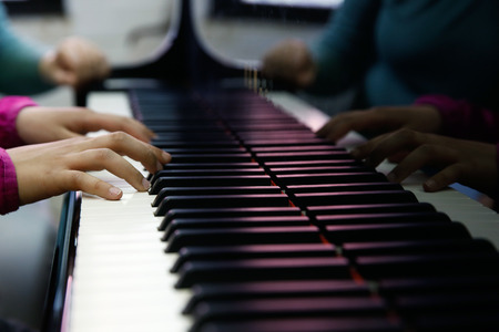 piano closeup: Teenager playing a piano, close-up on hands and keyboard. Rehearsal, school and discipline concept.