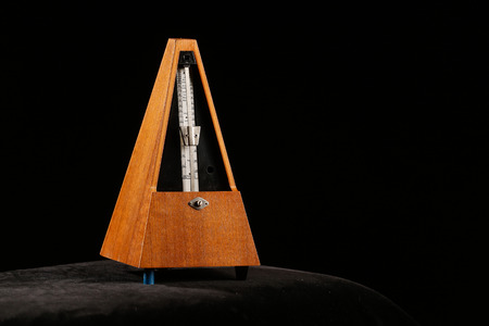 reiteration: Mechanical metronome giving tact by ticking certain beats per minute with pendulum swing. Basic device for professional composers and musicians.
