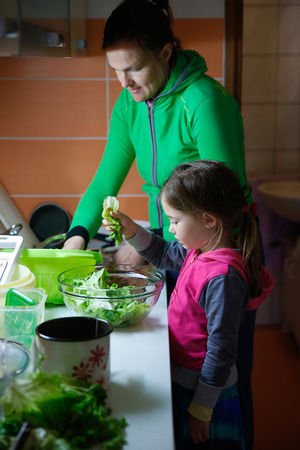 household chores: Mother and daughter working together, washing salad and preparing meal for the family in a messy kitchenette. Authentic situation of a child doing chores in the household, domestic help concept.