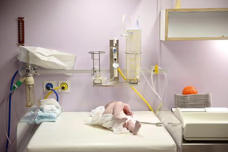 Pasgeboren bedekt met vernix direct na de bevalling. Kraamkliniek verloskamer, baby wordt beoordeeld voor Apgar score.