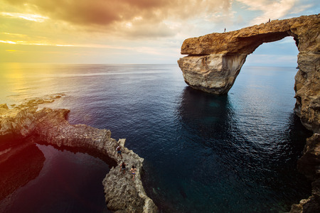 tourist spot: Azure Window, natural arch, famous landmark and popular tourist spot, on Gozo island, Malta, Mediterranean, at dramatic sunset. People walking on top of it, restricted area. Stock Photo