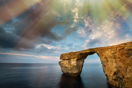 tourist spot: Azure Window, natural arch, famous landmark and popular tourist spot, on Gozo island, Malta, Mediterranean, with clouds, blue skies and dramatic sunrays.