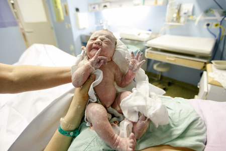 Mutter und Hebamme hält ein neugeborenes Baby, in Vernix direkt nach der Lieferung abgedeckt. Mutterschaftskrankenhaus Kreißsaal, baby ist zum ersten Mal mit Nabelschnur noch angebracht fotografiert. Standard-Bild
