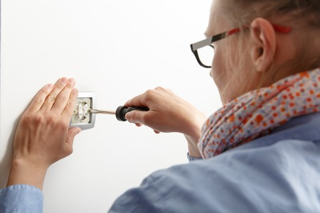 doityourself: Businesswoman installing a silver light switch with a screwdriver on a white wall, repairing an electrical problem by herself. Do-it-yourself (DIY) and emancipation concept.