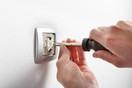 energy electrician: Electrician installing a silver light switch with a screwdriver on a white wall, renovating home.