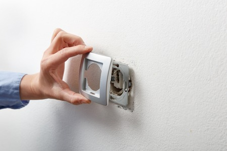 ac: Electrician installing a silver wall-mounted AC power socket with a screwdriver on a white wall, renovating home.
