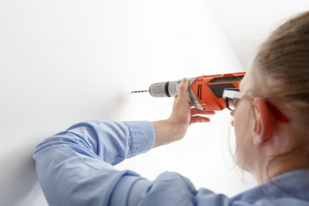 doityourself: Independent businesswoman holding electric power driller, drilling hole in a white concrete wall. Do-it-yourself (DIY) and emancipation concept.