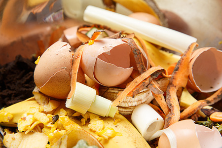 residual: Organic biological kitchen waste, rotten food and leftovers from cooking, prepared for composting. Egg shells, pumpkin, banana and carrot peel.