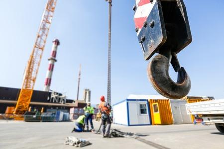 Haak van een mobiele hijskraan op een bouwplaats, kunnen heffen 25 ton lading met werknemers in de achtergrond. Heavy duty machines voor de zware constructie-industrie.
