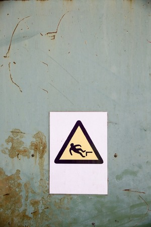 actual: Actual fall (trip) hazard sign, symbol warning workers and passers-by of danger and risk of falling, on uniform industrial rusty steel background. Safety and liability measures concept. Stock Photo
