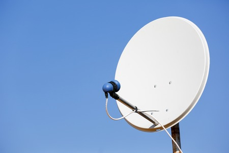 electromagnetic: Common residential satellite dish for reception of electromagnetic signals from satellites, on a blue sky background.