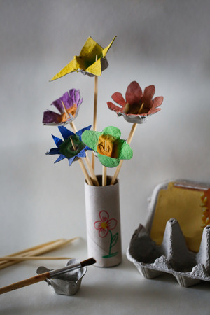 creative egg painting: Cut and painted egg carton flower bouquet, result of a waste reuse in creative activity with children. Spending quality time at home and creativity concept. Stock Photo