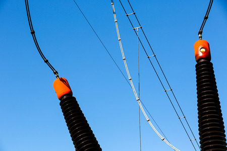 resistivity: Ceramic insulators of a converter transformer in electrical substation (transformer station). Blue sky background, power, energy and electricity concept. Stock Photo
