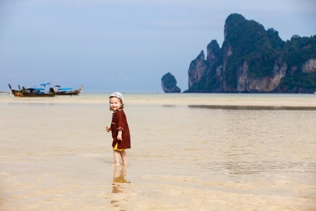 Child enjoying the low tides, walking on fine sand through the water on a tropical beach. Fearless, intrepid and adventurous childhood concept.