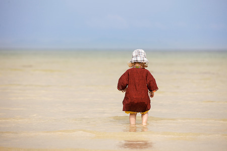 intrepid: Child enjoying the low tides, walking on fine sand through the water on a tropical beach. Fearless, intrepid and adventurous childhood concept.