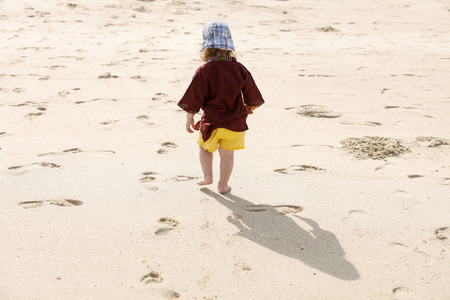 fearless: Fearless child leaving small steps in the sand, playing barefoot in the hot summer on a sandy beach.