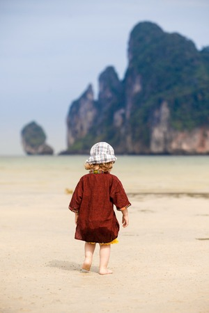 intrepid: Child enjoying the low tides, walking on fine sand on a tropical beach. Fearless, intrepid and adventurous childhood concept.