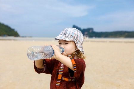 safe drinking water: Child on a trip to a sandy tropical beach in summer, drinking bottled water with soluble electrolytes for rehydration. Stock Photo