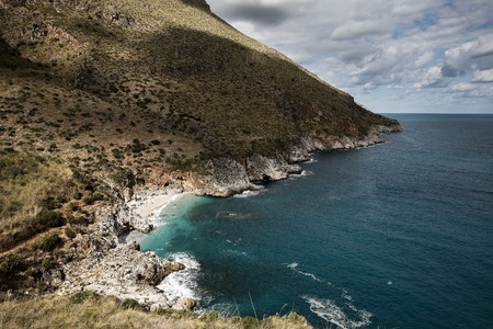 secluded: Romantic and secluded imposing paradise beach in Zingaro national park, Sicily, Italy, with turquoise waters and huge waves breaking on cliffed and rugged shore. Stock Photo