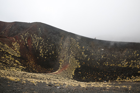 igneous: Scenery and craters of Mt. Etna volcano, Sicily, engulfed in thick clouds and fog, with sporadic yellow grasses growing on black volcanic (igneous) rock.