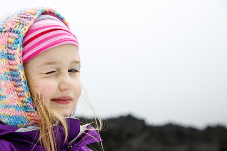 sneer: Portrait of playful and carefree, cute little Caucasian girl winking at mum and dad on a trip to Mt. Etna, Sicily, Italy. Active family lifestyle, traveling family concept.