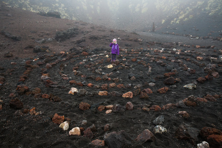 symbolism: Child standing in center of a spiritual spiral of igneous rock in Etna volcano crater. Spiral symbolizes centering and widening consciousness. Spirituality, symbolism and psychic concepts. Stock Photo