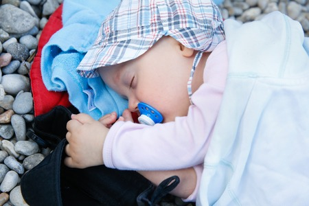 adaptable: Sleeping baby with a pacifier lying on a pebbled beach in improvised bed during a family vacation. Family on vacation, adaptable baby and relaxed parenting concept. Stock Photo