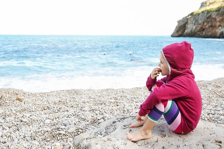 barefoot girls: Pensive girl relaxing on a pebbly beach, eating and observing the sea after swimming, barefoot and dressed in leggings and fleece. Family and children on vacation, late summer concept.