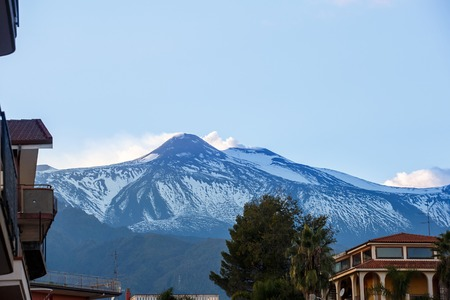 foothill: Summit of Mount Etna, active volcano in Sicily, Italy, spewing ash and gasses from its two erupting craters, photographed from the foothill town. Travel destination and forces of nature concept.