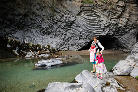 Mother with baby and little girl on an adventurous hiking trip through geologically interesting river gorge Golle del Alcantara in the foothills of Mt. Etna, Sicily, Italy. Family travel concept. photo