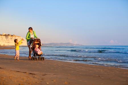 madre soltera: Individual madre recorre con su hija y su hijo, hablando y empujando un cochecito en una playa de arena a finales de verano, disfrutando del frío de la noche. Vacaciones familiares, viajar con niños concepto.