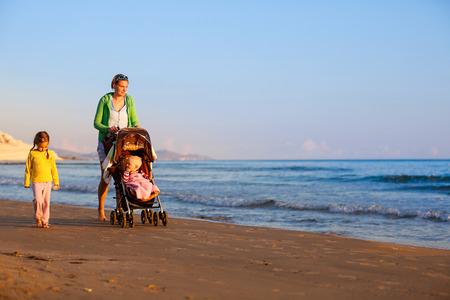 madre soltera: Madre soltera caminar en silencio con su hija y el bebé, empujando un cochecito en una playa de arena a finales de verano, disfrutando del frío de la noche. Vacaciones familiares, viajar con niños concepto.