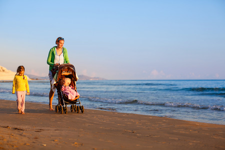 single parent: Single mother walking in silence with her daughter and baby, pushing a stroller on a sandy beach in late summer, enjoying the evening chill. Family vacation, traveling with children concept. Stock Photo
