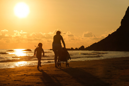 Silhouette of mother walking with her daughter and baby, pushing a stroller on a sandy beach in late summer, enjoying the evening chill. Family vacation, traveling with children concept. photo