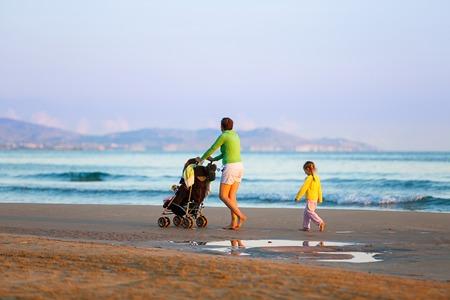 madre soltera: Madre soltera caminar en silencio con su hija y el bebé empuja un cochecito en una playa de arena a finales de verano disfrutando del frío de la noche. Vacaciones de familia viaja con niños concepto.