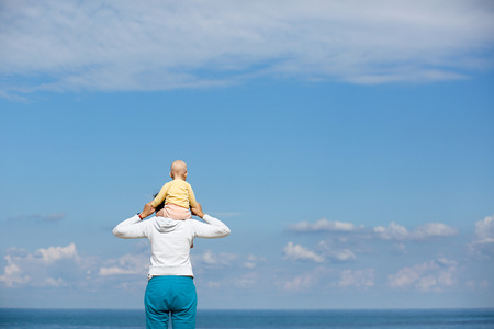 devoted: Devoted mother and baby cuddling, spending bonding quality time observing bright blue cloudscape and sea. Attentive parenting and family lifestyle concept. Nature and people background. Stock Photo
