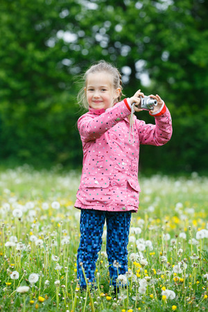 pursuing: Little smiling and curious girl photographing with her camera, exploring nature  and standing in a dandelion meadow. Active lifestyle, curiosity, pursuing a hobby concept.
