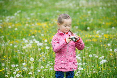pursuing: Little curious girl photographing with her camera, exploring nature and standing in a dandelion meadow. Active lifestyle, curiosity, pursuing a hobby concept.