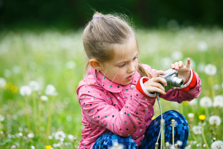 pursuing: Little curious girl photographing with her camera, exploring nature  up close and kneeling in a dandelion meadow. Active lifestyle, curiosity, pursuing a hobby concept.