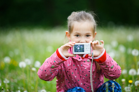 Little smiling girl proudly showing her photo on display, taken in a dandelion meadow. Active lifestyle, curiosity, pursuing a hobby, technology and kids concept. Stock Photo