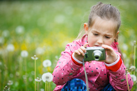 upclose: Little curious girl exploring nature with her camera, photographing up-close and kneeling in a dandelion meadow. Active lifestyle, curiosity, pursuing a hobby concept.