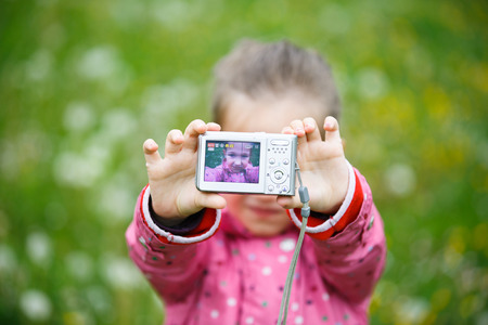 self conceit: Little cheerful girl making a selfie with digital camera, enjoying her time on a dandelion meadow. Active lifestyle, curiosity, pursuing a hobby, technology and kids  concept.
