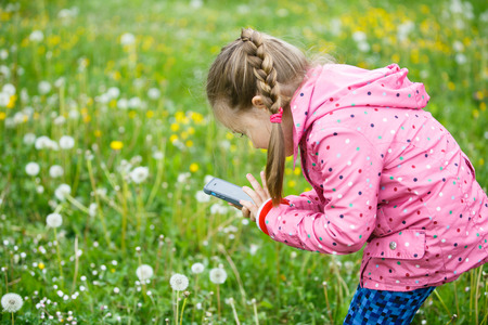pursuing: Little curious girl photographing up close with her smart phone, exploring nature  and standing in a dandelion meadow. Active lifestyle, curiosity, pursuing a hobby, technology and kids concept.