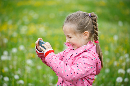 pursuing: Little smiling and curious girl photographing with her smart phone, exploring nature and walking on a dandelion meadow. Active lifestyle, curiosity, pursuing a hobby, technology and kids concept. Stock Photo