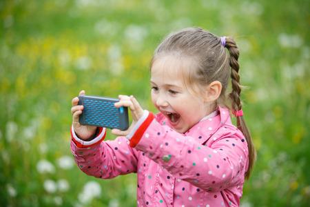 Piccola ragazza sorridente e curiosa che fotografa con il suo Smart Phone, esplorando la natura e stando in un prato del dente di leone. Stile di vita attivo, curiosità, ricerca di un hobby, tecnologia e concetto di bambini.