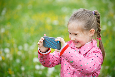 pursuing: Little smiling and curious girl photographing with her smart phone, exploring nature and standing in a dandelion meadow. Active lifestyle, curiosity, pursuing a hobby, technology and kids concept.
