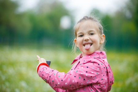 lively: Little girl making faces and showing her tongue to her father that disturbed her at taking a picture with smart phone. Disobedience, cheerful behavior and carefree childhood concept. Stock Photo